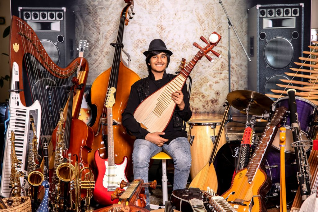 Neil Nayyar surrounded by many of the musical Instruments he loves play | California Pretty Magazine